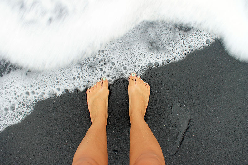 Feet on Black Sand Beach