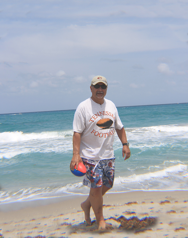 Papa Carrying Football on Beach