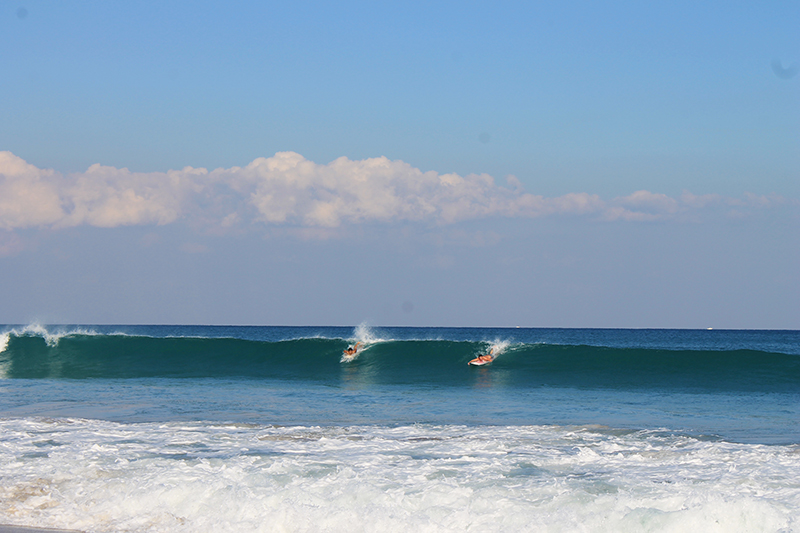 Two Surfers Catching Wave